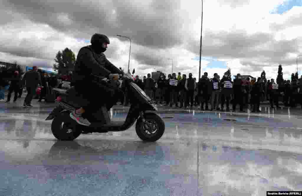 Një motoçiklist kalon pranë protestës së qumështarëve.