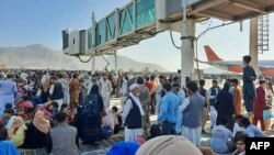 People crowd the tarmac of Kabul's airport on August 16, hoping to flee the country as the Taliban take in control of Afghanistan.