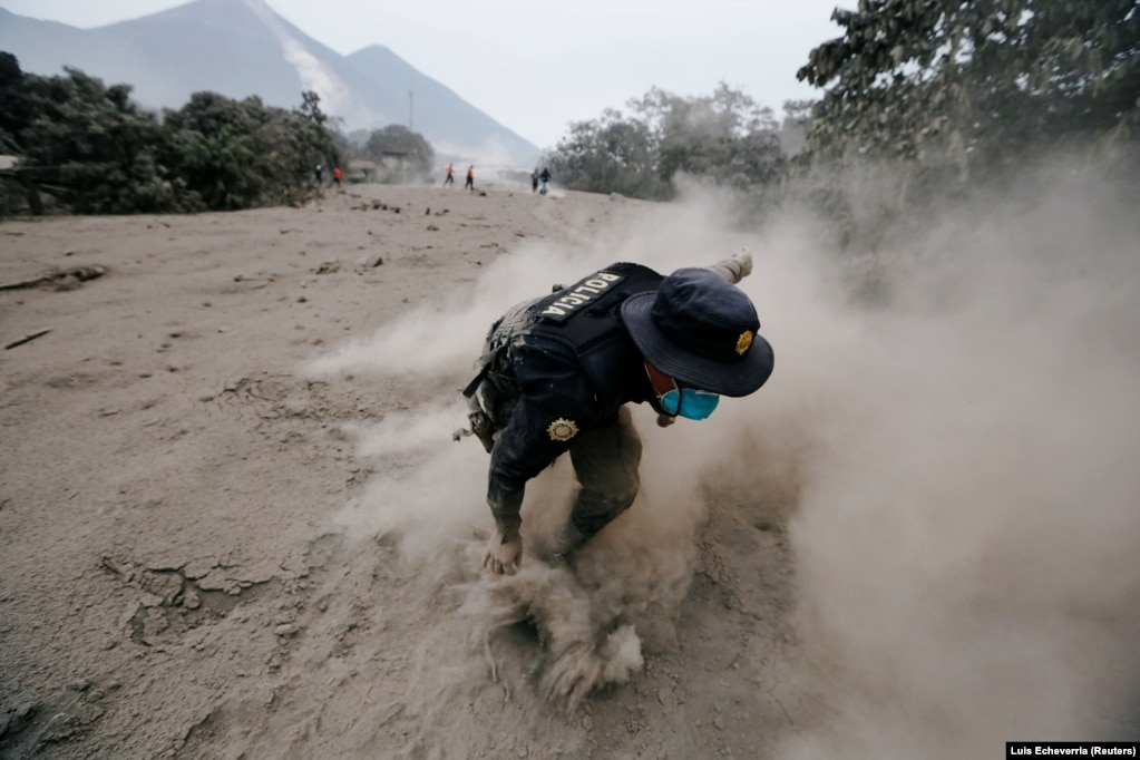 A police officer stumbles while running away after the Fuego volcano spew new pyroclastic flow in the community of San Miguel Los Lotes in Escuintla, Guatemala, on June 4. (Reuters/Luis Echeverria)