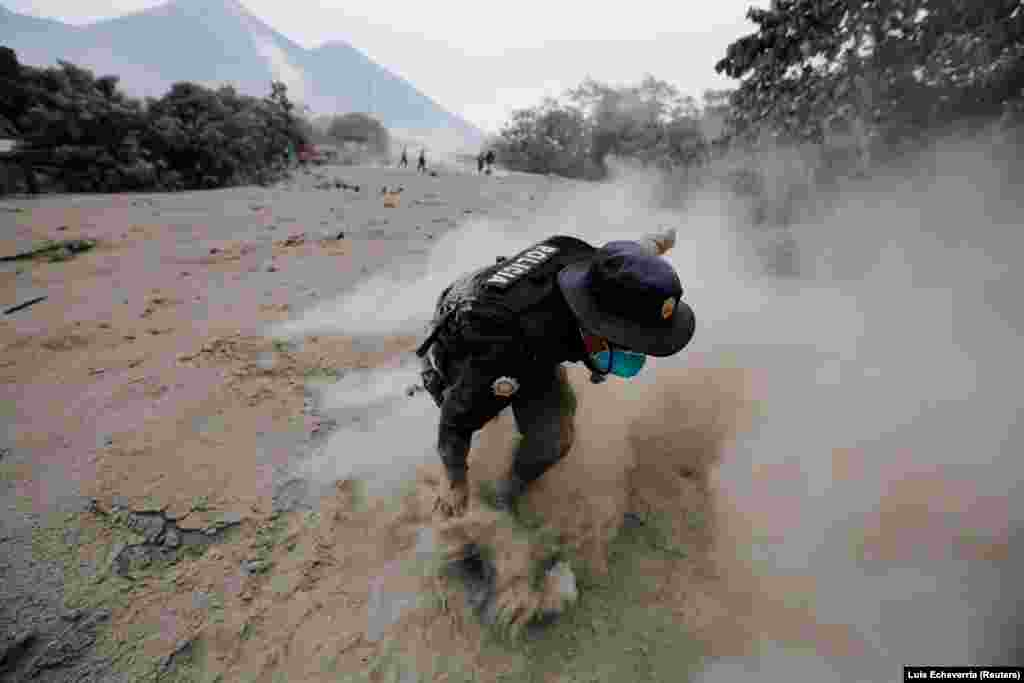 A police officer stumbles while running away after the Fuego volcano spewed a new pyroclastic flow in the community of San Miguel Los Lotes in Escuintla, Guatemala, on June 4. (Reuters/Luis Echeverria)