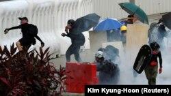 Протестующие бросают в полицию предметы после того, как был запущен слезоточивый газ, чтобы разогнать демонстрацию в поддержку общегородской забастовки и призвать к демократическим реформам в Гонконге, 5 августа 2019