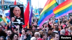 A demonstrator holds up a picture depicting Russian President Vladimir Putin with rainbow circles on his face, during a protest in Amsterdam on April 8.