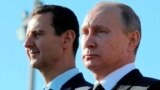 SYRIA -- Russian President Vladimir Putin (R) and Syrian President Bashar Assad watch the troops marching at the Hmeimim military base in Latakia Province, December 11, 2017