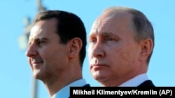 Russian President Vladimir Putin (R) and Syrian President Bashar Assad recently watching troops march in Syria