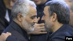 Commander of Quds force, Qassem Soleimani (left) shakes hands with President, Mahmoud Ahmadinejad, in the funeral of his mother, 2013.