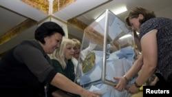 Члены избирательной комиссии открывают урну с бюллетенями после закрытия избирательного участка в Алматы. 26 апреля 2015 года.