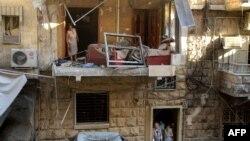 Алеппо тұрғындары зымыран соққысынан бүлінген ғимаратты қарап тұр. 11 шілде 2016 жыл.