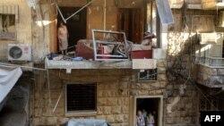 Жители Алеппо смотрят на разрушенные строения после ракетного обстрела. 11 июля 2016 года.