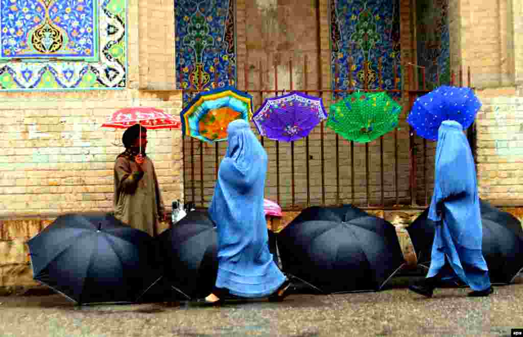 An Afghan man sells umbrellas on a roadside in Herat. (epa/Jalil Rezayee)