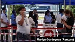 Люди стоят в очереди у центра тестирования на COVID-19 в Алматы.