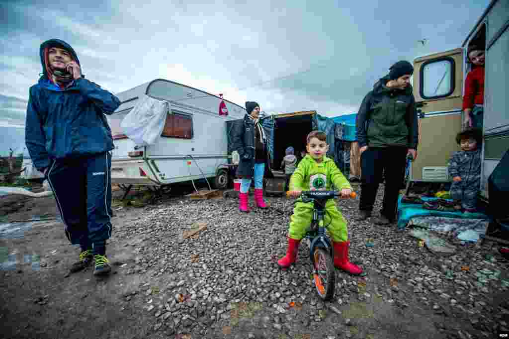 A refugee family stands in front of their caravan the day before Christmas in a camp nicknamed 'The Jungle' in the French port of Calais. (epa/Stephanie Lecocq)