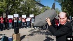 Человек в маске Путина с макетом бомбы перед российским посольством в Берлине во время демонстрации против действий России в Сирии