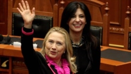 U.S. Secretary of State Hillary Clinton (left) waves after speaking to the Albanian parliament in Tirana, as speaker Josefina Topalli walks beside her.