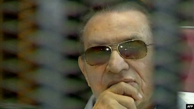 Ousted Egyptian leader Hosni Mubarak sits behind the defendant's cage during a trial in Cairo earlier this summer. (file photo)