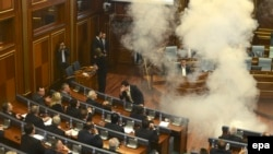 Opposition lawmakers throw tear gas during a session of Kosovo's parliament in Pristina on October 8.