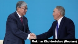 Kazakh interim President Qasym-Zhomart Toqaev (left) and former President Nursultan Nazarbaev shake hands at the congress of the ruling Nur Otan ruling party in Nur-Sultan on April 23.