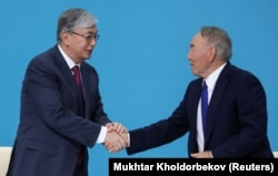 Interim Kazakh President Qasym-Zhomart Toqaev (left) and longtime President Nursultan Nazarbaev attend a congress of the Nur Otan ruling party in the capital, Nur-Sultan, on April 23.