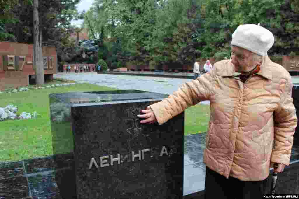 Лидер Алматинской городской организации жителей блокадного Ленинграда Марина Сергиева показывает следы вандализма на тумбе, посвященной городу-герою Ленинграду.