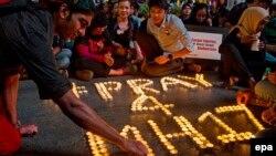 Молодые малайзийцы зажигают свечи в память о погибших при авиакатастрофе