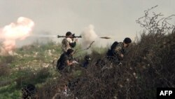Syria -- A video grab shows an opposition fighter firing an rocket propelled grenade (RPG) during clashes with regime forces over the strategic area of Khanasser,, August 26, 2013