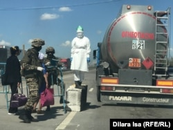 Soldiers and a doctor man a checkpoint at the entrance to Shymkent, Kazakhstan, on April 30.
