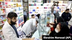 Pharmacists talk with customers at a drugstore in downtown Tehran, February 25, 2020
