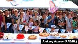 Группа людей смотрит на конкурсные пироги и ожидает решения жюри на праздничных мероприятиях ко Дню города. Алматы, 16 сентября 2012 года.