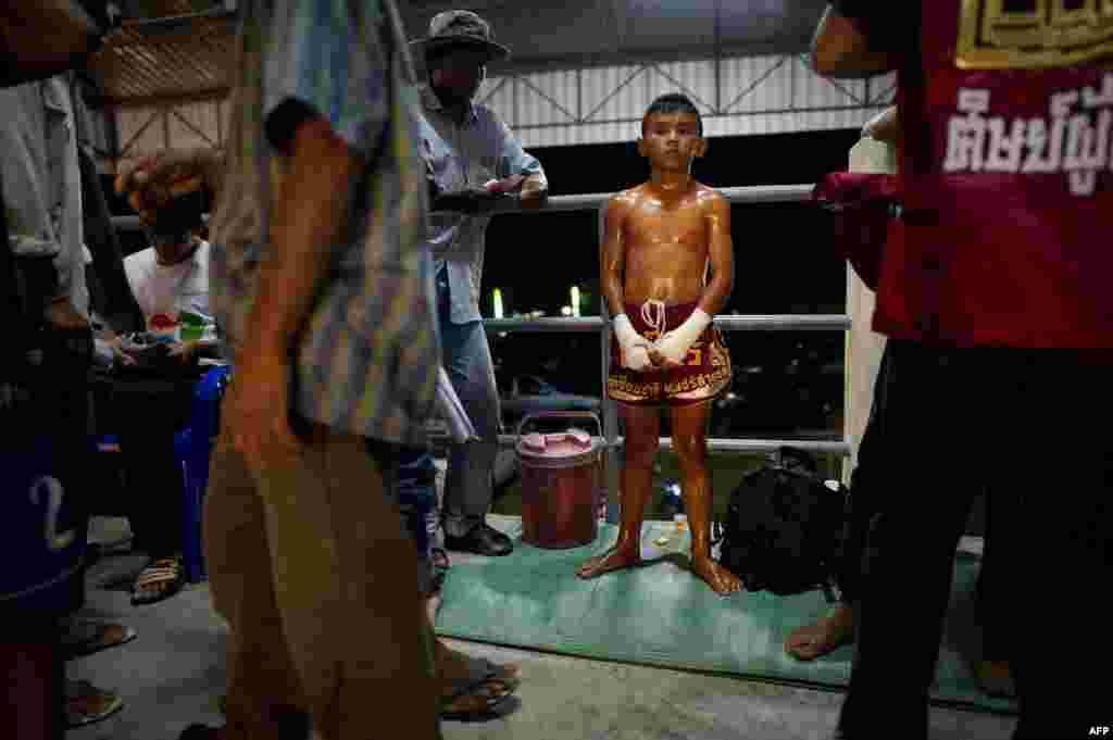 A Muay Thai boxer waiting for his fight next to his coach counting money