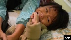 Индонезийская девочка плачет во время процедуры обрезания