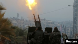 Free Syrian Army fighters firing an antiaircraft weapon in a rebel-held area of Aleppo in December