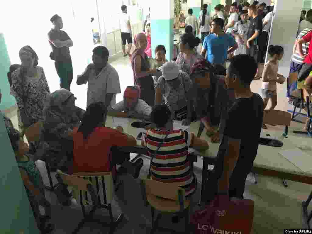 Люди отмечаются в списке в эвакуационном пункте при школе № 87 города Шымкента.