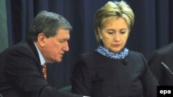 U.S. Secretary of State Hillary Clinton (right) talks with Ambassador Richard Holbrooke during a trilateral meeting with Afghan and Pakistan delegations at the State Department on February 26.
