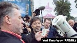 Ведущий митинга-концерта Артемий Троицкий осваивает непривычную звукоаппаратуру