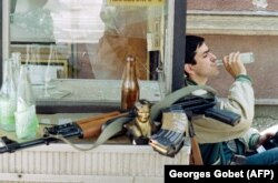 A Bosnian fighter sips a drink next to his Kalashnikov and a statuette of Marshal Tito, the former leader of Yugoslavia, in the Bosnian capital, Sarajevo, in 1992.