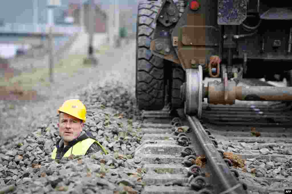 A Belgian engineer works on train tracks in Profondeville. The modernization of the line will enable the system to automatically stop a train that neglects a red light or exceeds the maximum speed limit. (AFP/Belga/Bruno Fahy)