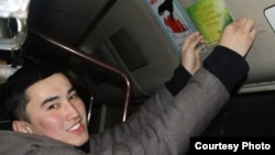 Студент приклеивает листовку с пословицей в общественном транспорте. Семей, 22 января 2013 года. Фото Асель Шайхыновой.