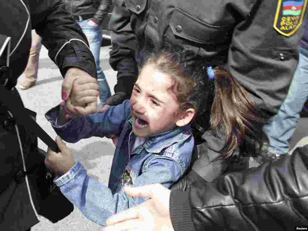 "Police apprehend a girl after she shouted ""freedom"" during an opposition rally in Baku on April 17. The girl and her mother were both taken away in a police car. (Reuters/Irada Humbatov)"