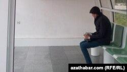 Aşgabadyň awtobus duralgalarynyň birinde oturan türkmen oglany.