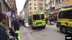 Emergency services help the injured near the scene where a truck crashed into a department store in central Stockholm in April. An Uzbek man has been charged with deliberately ramming the shop, killing four people.