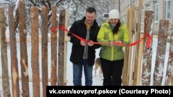 Former regional lawmaker Arkady Vasilyev and union leader Ulyana Mikhailova ceremonially open a fence at a Pskov school that is meant to protect students from a terrorist attack.