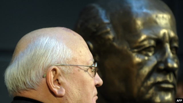 Mikhail Gorbachev stands next to a bust of himself after unveiling it in Berlin in November 2009.