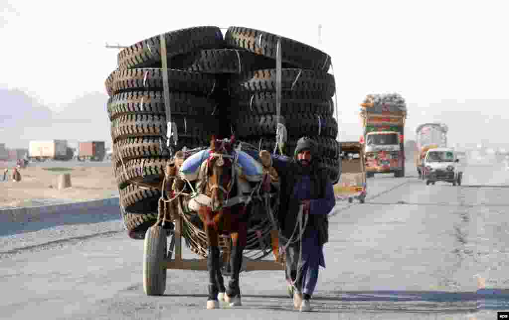 A man tends his horse-drawn cart, which is loaded with tires, near the Afghan border in Chaman, Pakistan. (epa/Akhter Gulfam)