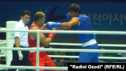 Ҷаҳон Қурбонов (аз тарафи рост) ҳангоми рақобат дар майдони бокс