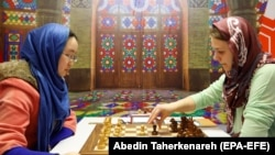 Chinese player Tan Zhongyi (L) faces Anna Muzychuk (R) of Ukraine in the first game of their Women's World Chess Championship final in Tehran, February 28, 2017