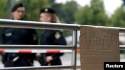 """""""Warum"""" (Zašto) piše na jednom kartonu na mestu ubistva civila ispred šoping centra """"Olimpija"""", Minhen, 23. jul 2016."""