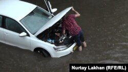 Водитель пытается завести машину, заглохшую из-за затопления улицы. Алматы, 17 июня 2016 года.
