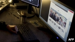 France -- A masked hacker, part of the Anonymous group, hacks the presidential Elysee Palace website, 20Jan2012