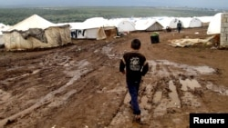 A refugee boy walks through mud at a refugee camp in Atimeh, on the Syrian-Turkish border of the Idlib Governorate.