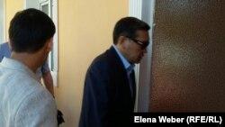 Бывший премьер-министр Казахстана Серик Ахметов (в центре) входит в зал суда. Караганда, 28 июля 2015 года.