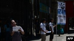 Добровольцы раздают листовки с призывом участвовать в неофициальном референдуме в Макао